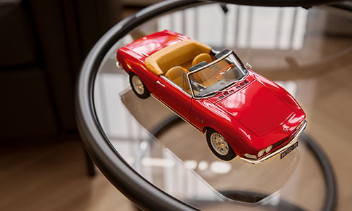 Rotes Modell-Auto liegt auf einem Glastisch in der Bank Baumann & Cie